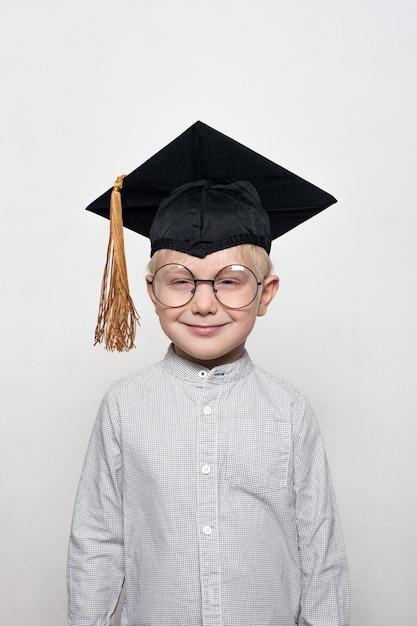 Portret van een schattige blonde jongen in grote glazen en een academische hoed. Premium Foto