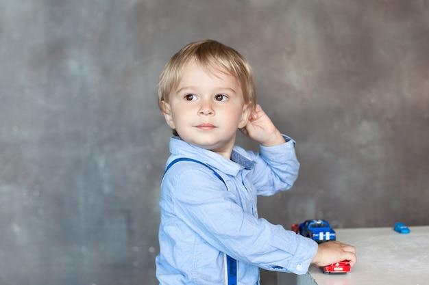 Portret van een schattige kleine jongen die met kleurrijke stuk speelgoed auto's speelt. actieve jongen speelt met speelgoedauto's in de kleuterschool. het concept van de ontwikkeling van kinderen en kinderen. kind thuis in de kinderkamer. baby thuis Premium Foto