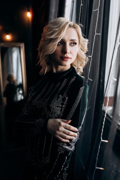 Portret van een schattige vrouw in zwarte jurk poseren in een gezellige donkere kamer met kerst decor Gratis Foto