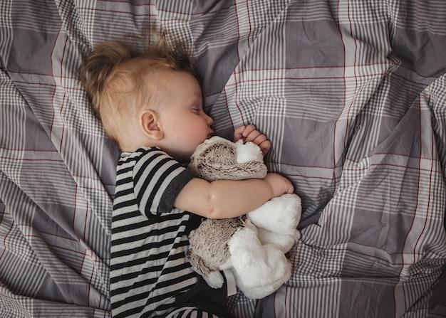 Portret van een schattige zes maanden oude blonde jongen slapen op een grijs bed met een stuk speelgoed in zijn handen Premium Foto
