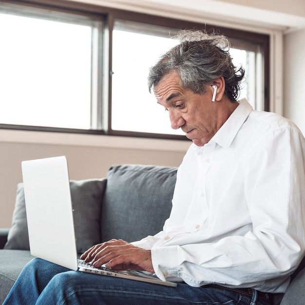 Portret van een senior man zittend op de bank dragen van bluetooth oortelefoon met behulp van laptop Gratis Foto