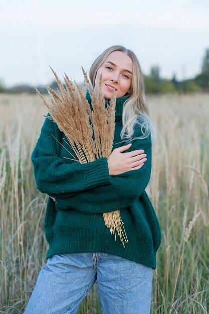 Portret van een sensuele blonde jonge vrouw in tarwe op een zomeravond. Premium Foto
