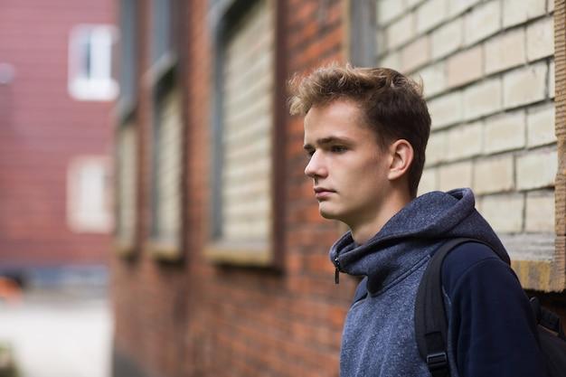Portret van een serieuze tiener tegen een bakstenen muur Premium Foto