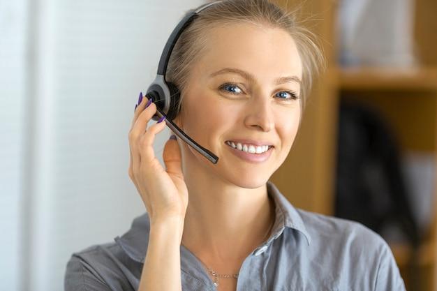 Portret van een smileyvrouw met hoofdtelefoon die in een call centre werkt. detailopname. Premium Foto