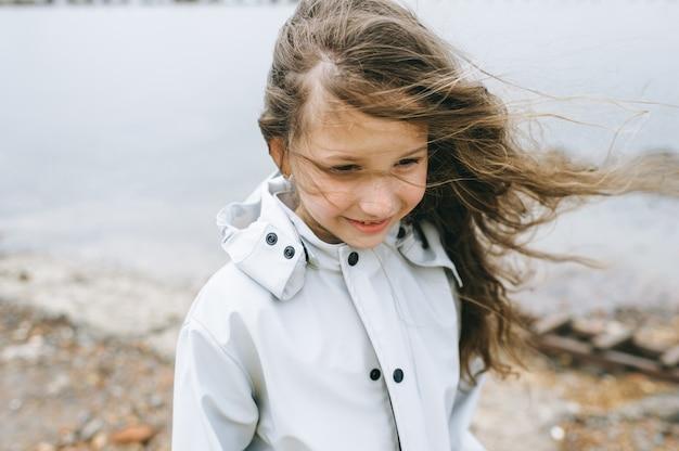 Portret van een smilling meisje in de buurt van de zee in de regenjas Premium Foto
