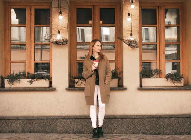 Portret van een stijlvolle dame van volledige lengte, staande met een kopje koffie in haar handen, gekleed in een jas tegen de achtergrond van de muur van het café, zijwaarts kijkend Premium Foto