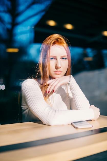 Portret van een stijlvolle jonge vrouw zitten in café Gratis Foto