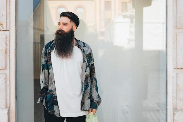 Portret van een stijlvolle man met shirt staande voor glas Gratis Foto