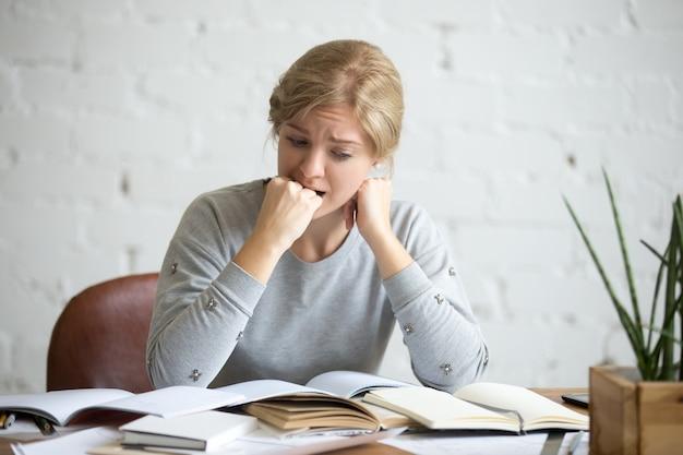 Portret van een student meisje zit aan het bureau bijt haar vuist Gratis Foto