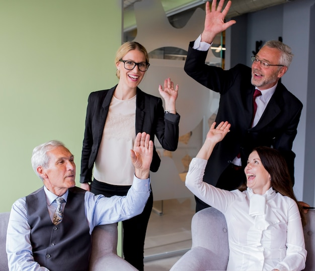 Portret van een succesvolle groep zwaaien handen in kantoor Gratis Foto