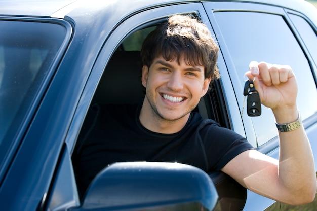 Portret van een succesvolle jonge gelukkig man met de sleutels zitten in een nieuwe auto Gratis Foto