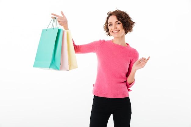 Portret van een tevreden gelukkig meisje dat het winkelen zakken toont Gratis Foto