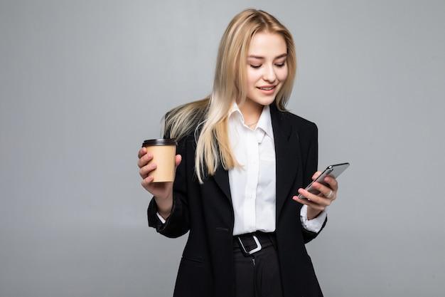 Portret van een tevreden jonge bedrijfsvrouw die mobiele telefoon met behulp van terwijl het houden van kop van koffie geïsoleerd te gaan Gratis Foto