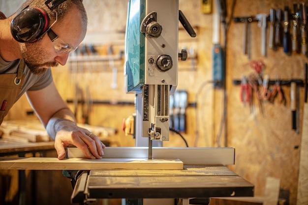 Portret van een timmerman binnen zijn timmerwerkworkshop die een lintzaag gebruikt. Premium Foto