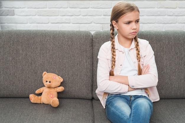 Portret van een triest meisje met gekruiste armen zitten in de buurt van de teddybeer op grijze bank Gratis Foto