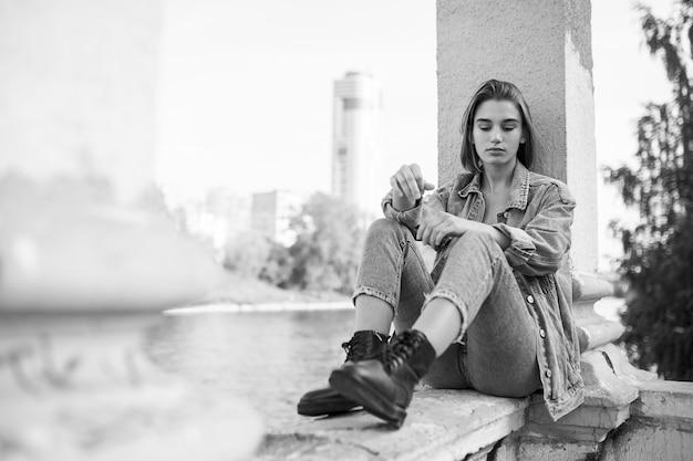 Portret van een verlangen peinzende tiener, gekleed in denim en laarzen, zittend. horizontaal zicht. Premium Foto