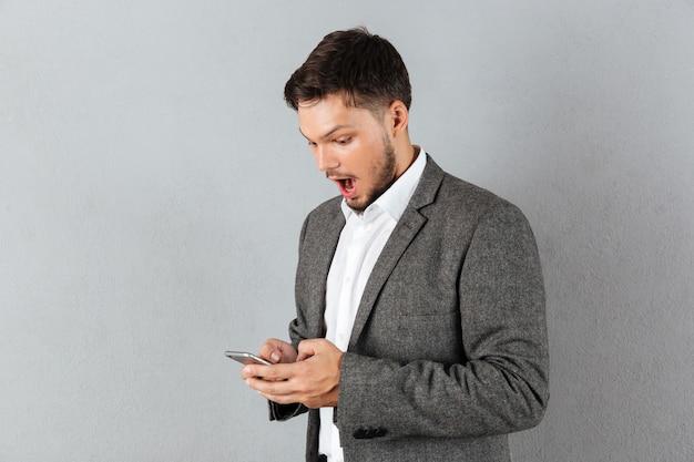 Portret van een verraste zakenman die mobiele telefoon bekijkt Gratis Foto