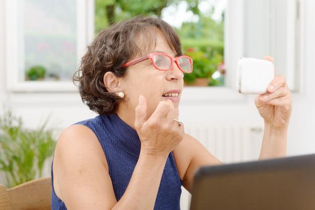 Portret van een volwassen vrouw met een telefoon Premium Foto