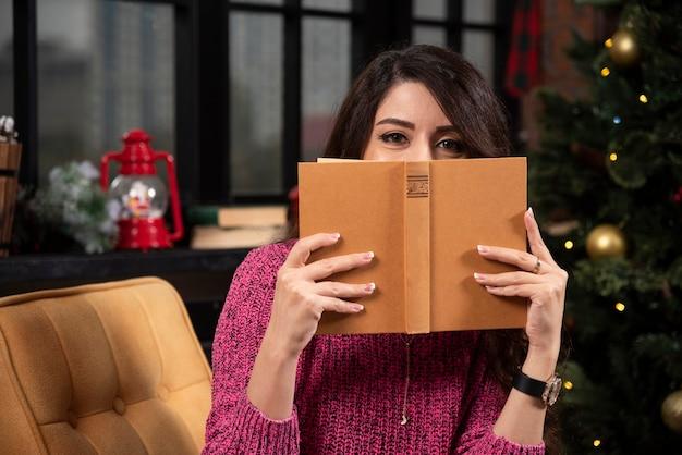 Portret van een vrij jong meisje dat zich achter een open boek verstopt. Gratis Foto