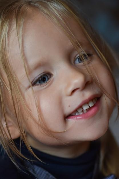 Portret van een vrolijk romantisch meisje met grote blauwe ogen en een open glimlach van oost-europa, close-up, donkere achtergrond Premium Foto