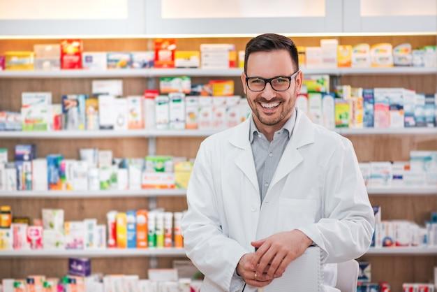 Portret van een vrolijke gezondheidszorgarbeider in witte laag bij farmaceutische opslag. Premium Foto