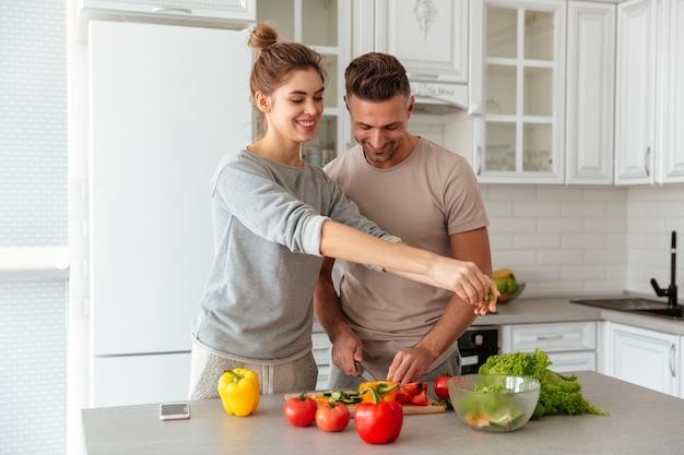 Portret van een vrolijke houdende van paar kokende salade samen Gratis Foto