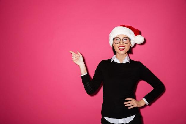 Portret van een vrolijke jonge zakenvrouw met kerstmuts Gratis Foto