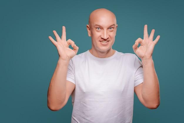 Portret van een vrolijke mens die ok gebaar toont dat op de blauwe achtergrond wordt geïsoleerd Premium Foto