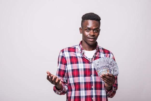 Portret van een vrolijke opgewonden afro-amerikaanse man die geldbankbiljetten houdt en geïsoleerd kijkt Gratis Foto
