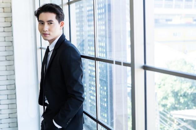 Portret van een vrolijke volwassen aziatische jonge zakenman draagt een pak van man in blauwe jas en blauw shirt kijken naar het raam in de kantoorruimte achtergrond. Premium Foto