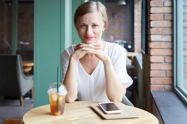 Portret van een vrolijke vrouw die camera bekijkt en bij de koffielijst glimlacht Gratis Foto