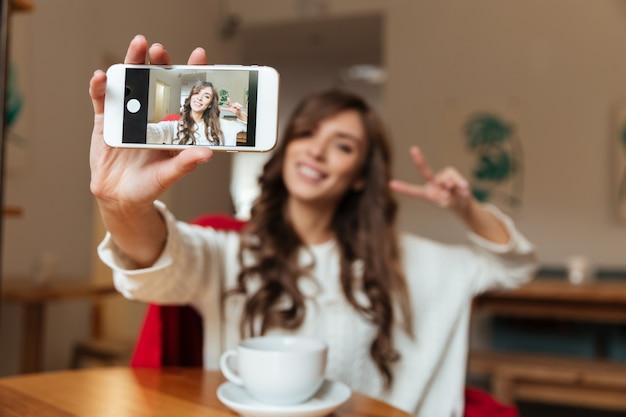 Portret van een vrolijke vrouw die een selfie neemt Gratis Foto