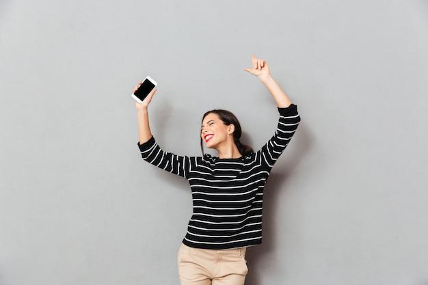 Portret van een vrolijke vrouw die mobiele telefoon houdt Gratis Foto