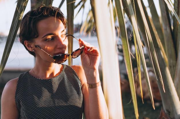 Portret van een vrouw achter palmbladen Gratis Foto