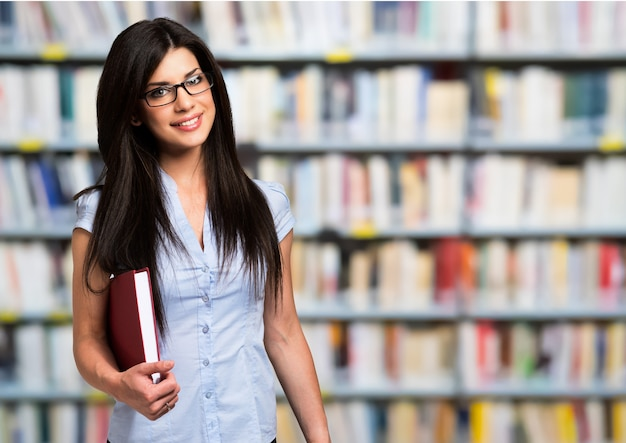 Portret van een vrouw die een boek in een bibliotheek houdt Premium Foto