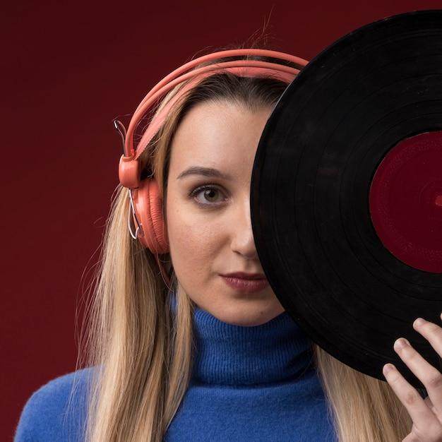 Portret van een vrouw die een vinylschijf houdt Gratis Foto