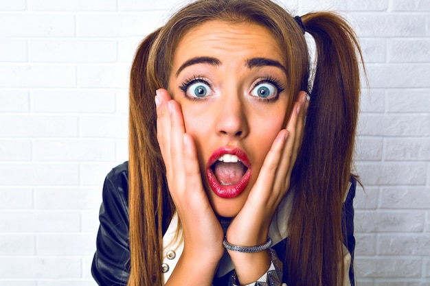 Portret van een vrouw die eng grappig verrast emotionele dagen, twee paardenstaarten en lichte make-up close-up. Gratis Foto