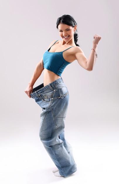 Portret van een vrouw die haar gewichtsverlies toont Gratis Foto