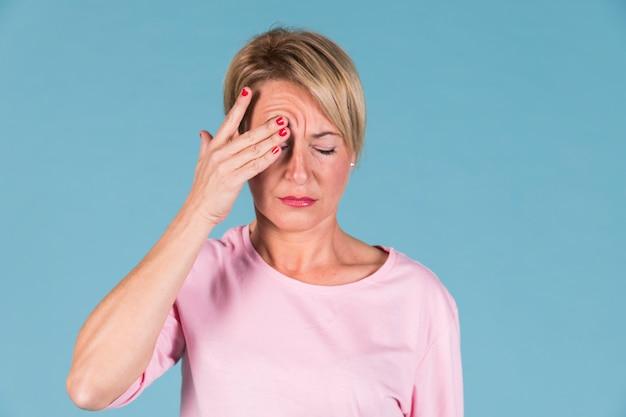 Portret van een vrouw die zijn hoofd in pijn houdt Gratis Foto