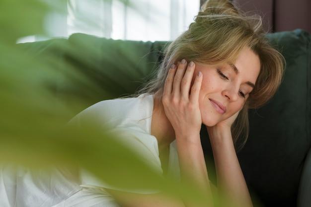 Portret van een vrouw en een wazig kamerplant Gratis Foto
