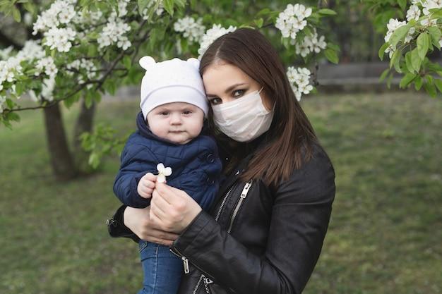 Portret van een vrouw en haar zoon in een beschermend masker tegen het kroonvirus of een uitbraak van het covid-19 en pm 2.5-virus in de stad Premium Foto