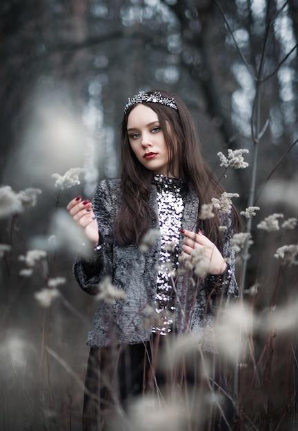 Portret van een vrouw in een sprookjebeeld van een donkere koningin in een mysterieus bos Premium Foto