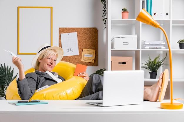Portret van een vrouw in het kantoor bereid voor de zomervakantie Gratis Foto