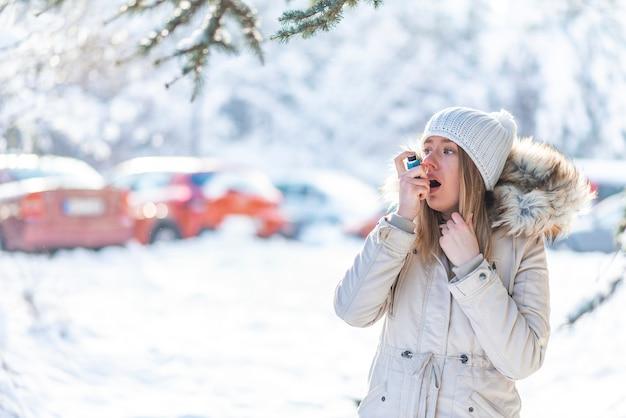 Portret van een vrouw met behulp van een astma-inhalator in een koude winter Premium Foto