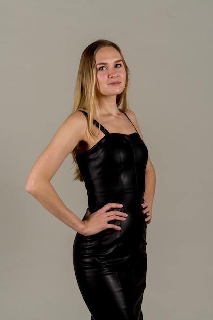 Portret van een vrouw met een puistig gezicht in een leren zwarte jurk. Premium Foto