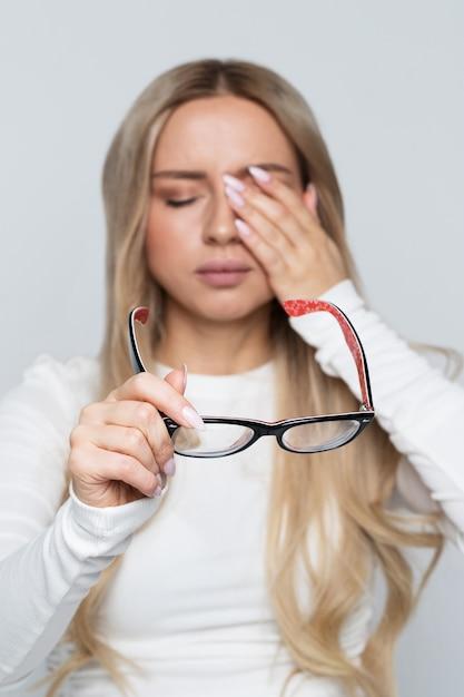 Portret van een vrouw met haar bril terwijl ze haar ogen wrijft Premium Foto
