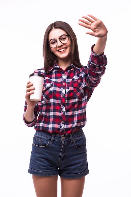 Portret van een vrouw met hallo gebaar drinkt thee of koffie uit papieren beker op wit. Gratis Foto