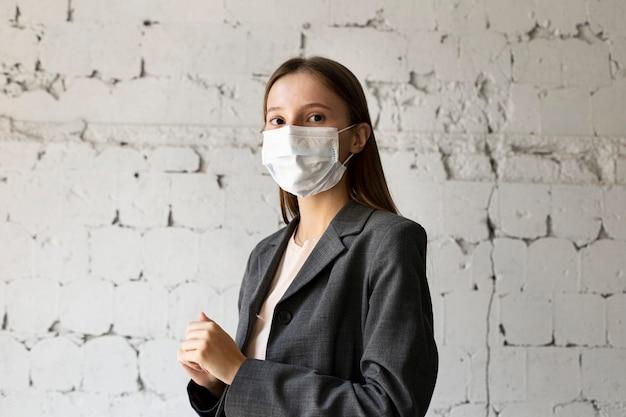 Portret van een vrouw op kantoor met gezichtsmasker Gratis Foto