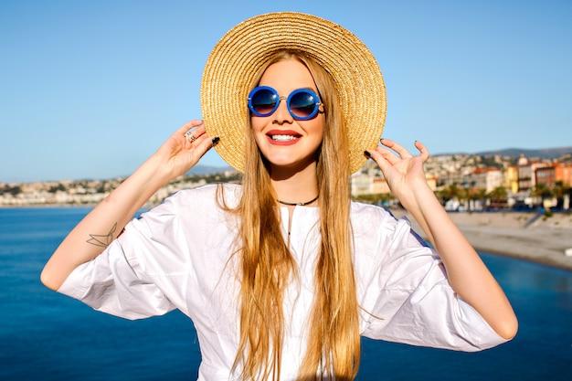 Portret van een vrouw poseren in de buurt van blauwe zee Gratis Foto