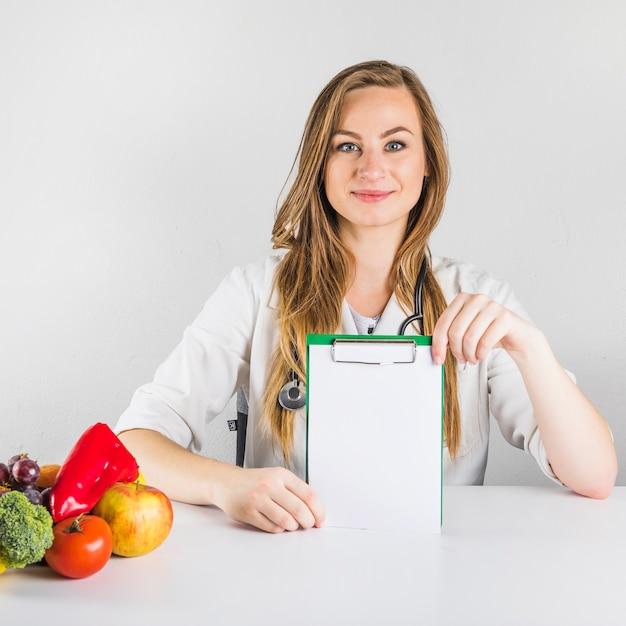 Portret van een vrouwelijke diëtist die leeg klembord met gezond voedsel op bureau houden Gratis Foto